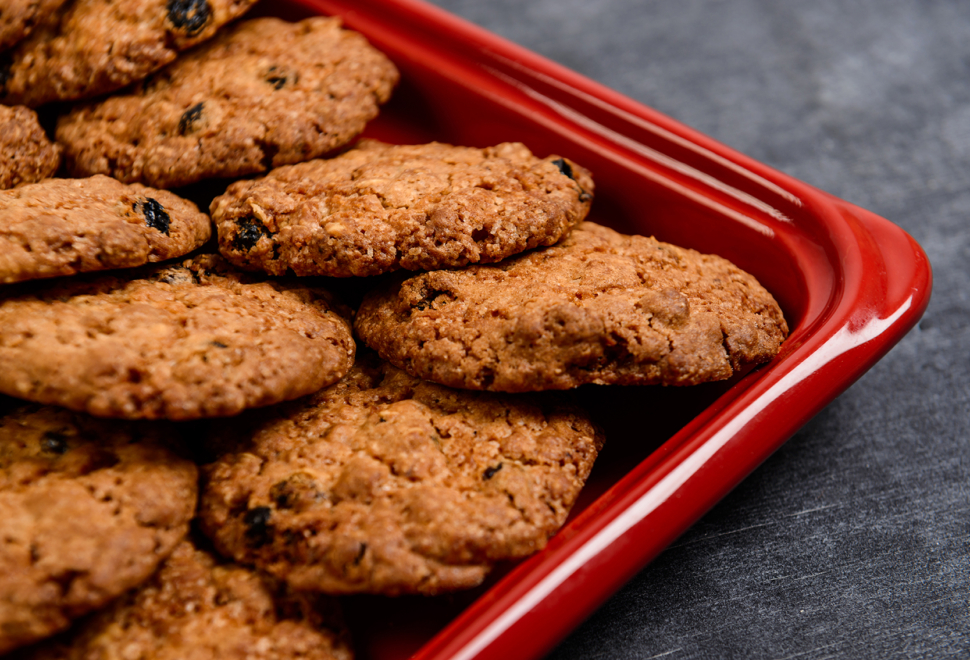 Sweet oatmeal cookies in red tray on wooden table