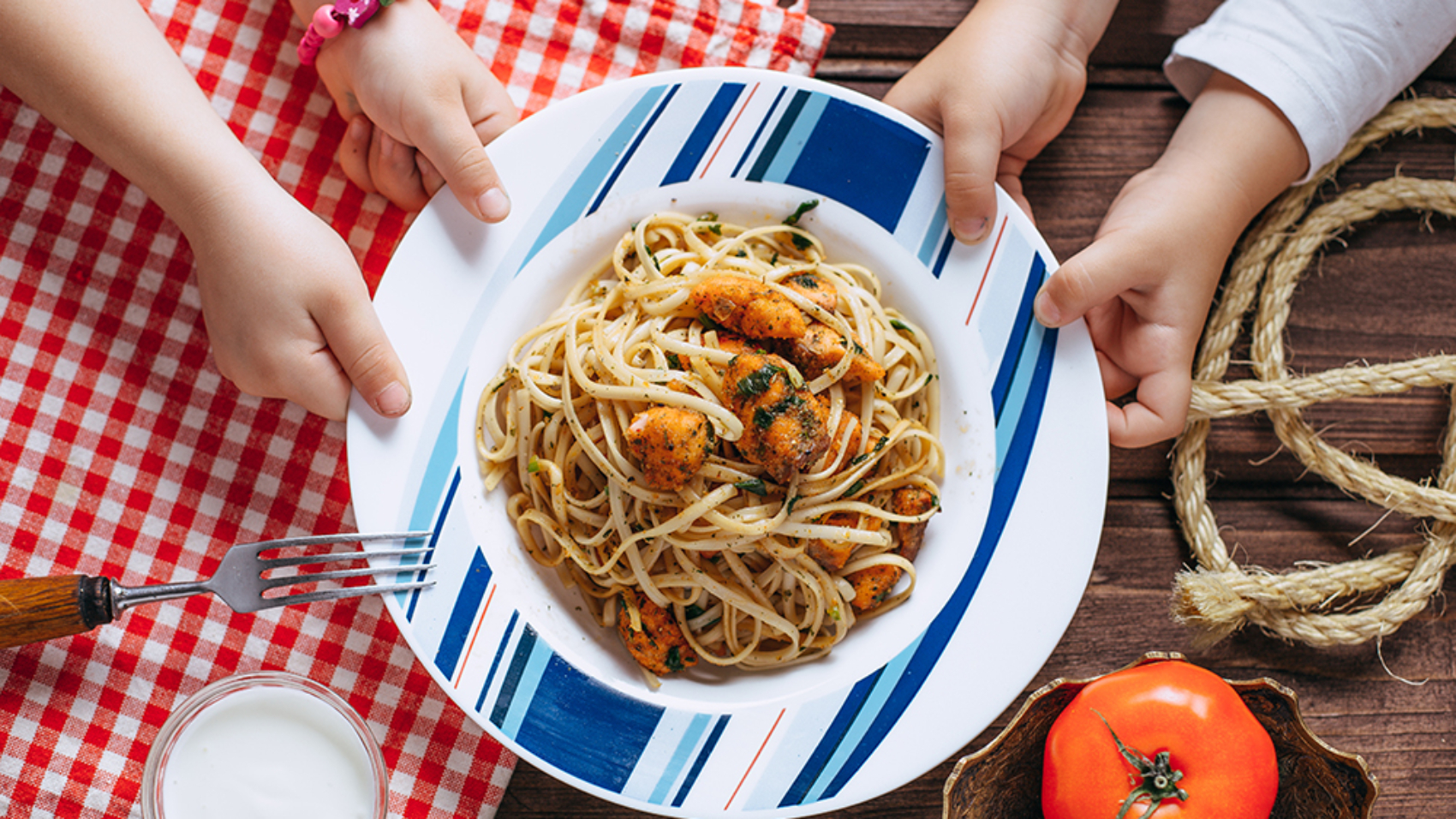 Kids hands and plate with pasta on table , cooking at home with baby top view